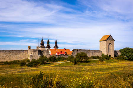 Beautiful rural summer view of an ancient medieval brick tower and defense wall surrounding the city of Visby Gotland, Sweden. Blue sky and grassy fields.