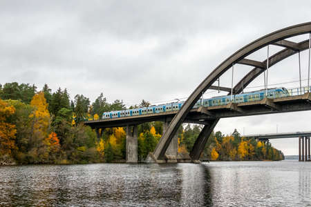 Nature autumn landscape scene with large arch concrete bridge with train crossing over calm water.