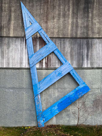 Blue wooden outdoor structure, shape as an arrow on dirty rough concrete wall.
