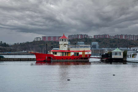 Urban winter scene with a red lighthouse light ship houseboat with dramatic clouds and buildings in the background. Stock Photo