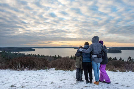 Family together holding each other and looking at a view. Mountain top winter sunset snow scene with water and horizon.
