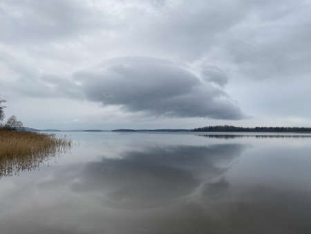 Soft cloud formation of one cloud over water. Beautiful tranquil gray winter scene.