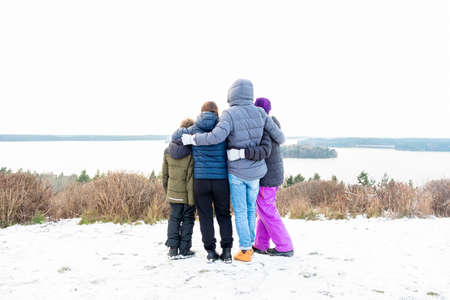 Family together holding each other and looking at a view. Mountain top winter snow scene with water and horizon.