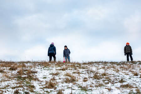 Low angle view of three children outdoor on a grassy snow hill with sky in the background.