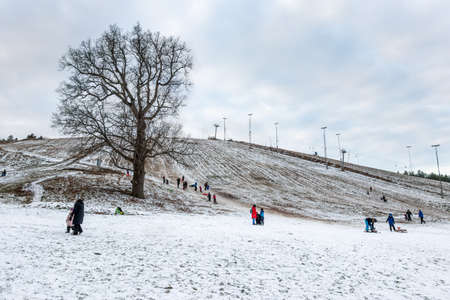 JARFALLA, SWEDEN - JANUARY 9, 2021: People outdoor having fun in the snow skiing and sledding on big grassy hill with snow in Jarfalla Sweden January 9, 2021. Editorial