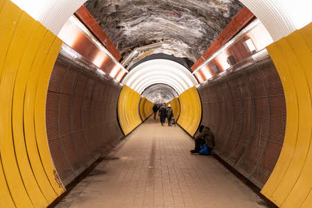 STOCKHOLM, SWEDEN - FEBRUARY 13, 2021: Perspective view of people in the pedestrian tunnel Brunkebergstunneln in Stockholm Sweden February 13, 2021.