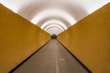 Perspective view of long modern futuristic yellow underground pedestrian tunnel in Stockholm Sweden.