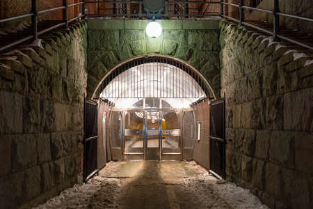 Beautiful night scene of massive stone wall and arch with bright lamp over pedestrian underground tunnel entrance in Stockholm Sweden.