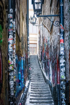STOCKHOLM, SWEDEN - FEBRUARY 13, 2021: Perspective view of narrow street with snowy steps and stickers on lamp posts in The Old Town in Stockholm Sweden February 13, 2021.