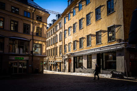 STOCKHOLM, SWEDEN - FEBRUARY 13, 2021: Light and dark shadows on buildings in The Old Town with a woman crossing snowy square in Stockholm Sweden February 13, 2021.