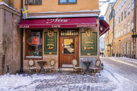 STOCKHOLM, SWEDEN - FEBRUARY 13, 2021: City winter scene with snow. Exterior of old vintage little café in the Old Town in Stockholm Sweden February 13, 2021.
