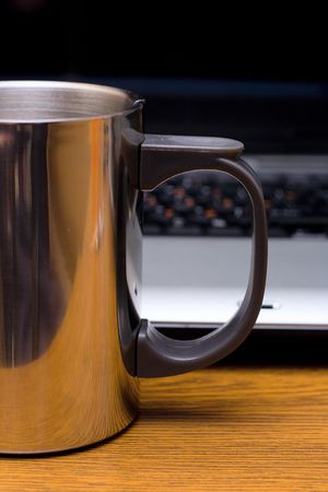 metal cup before laptop, on wooden table photo