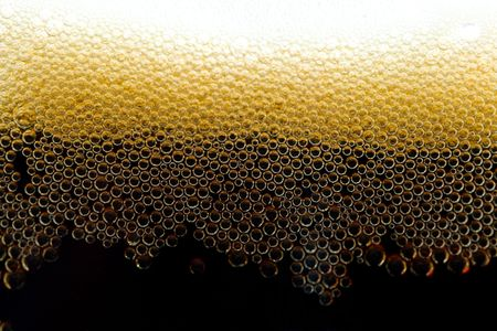 unstrained: close-up appetizing dark beer with bubbles
