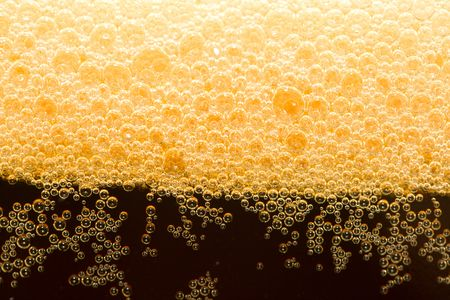 unstrained: close-up appetizing filtered dark beer with foam Stock Photo