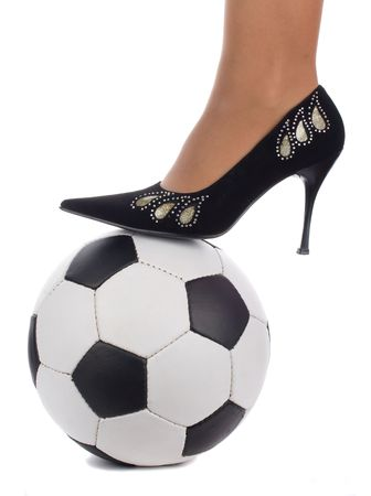 woman foot in high-heeled shoe stand on soccer ball, isolated on white photo