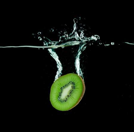 kiwi falling into water, isolated on black photo