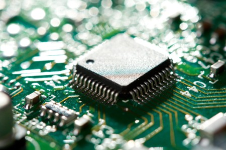 miniaturization: close-up chip on green circuit board, selective focus Stock Photo