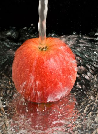 spilling: red apple under water stream on black Stock Photo