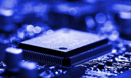 microelectronics: close-up chip on circuit board with selective focus, blue toned Stock Photo