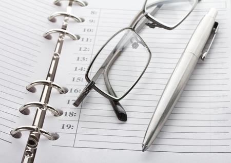 emploi du temps: lunettes, stylo et close-up notebook