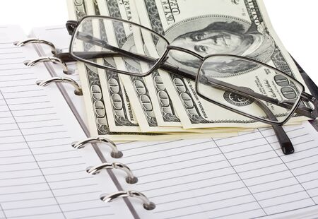 close-up opened notebook, dollars and glasses photo