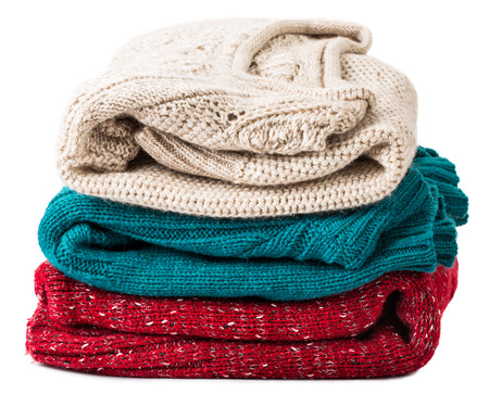 close-up Stack of warm sweaters, isolated on white