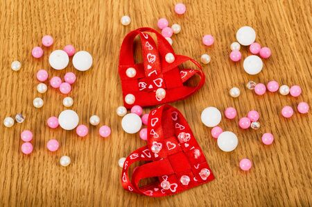 two hearts with beads on wooden background Stock Photo