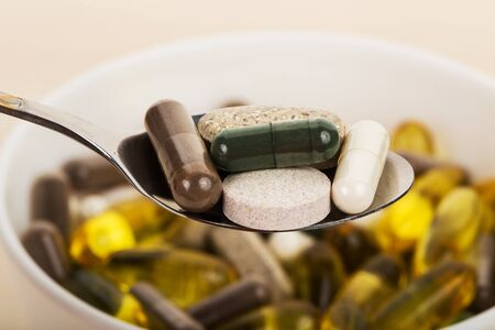 malnutrition: close-up dietary supplement capsules and tablets in spoon