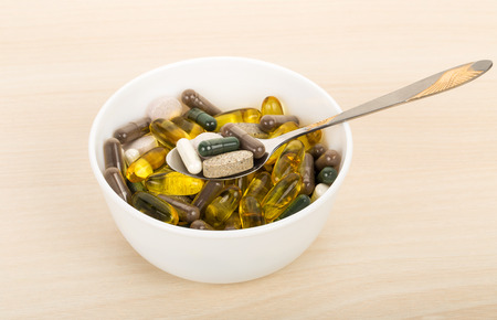 close-up dietary supplement capsules and tablets in bowl with spoon Stock Photo
