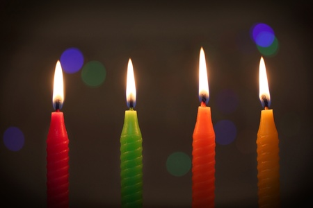 candles in dark: Four colored candles on dark bokeh background Stock Photo