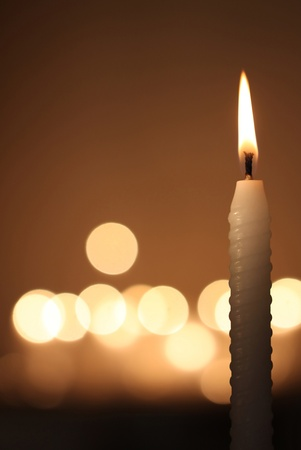 memorial candle: white candle on dark bokeh background