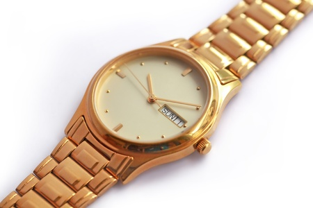 A golden colored watch set to 10:10 sunday day 1