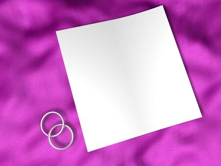 white paper and wedding rings on pink silk textile