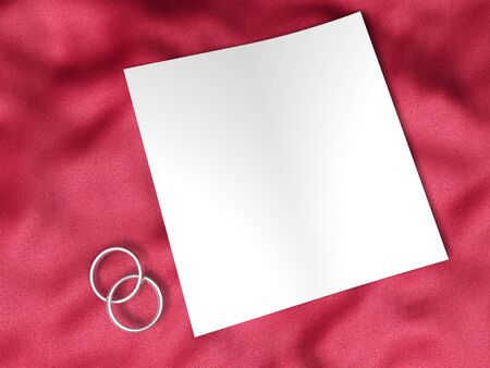 white paper and wedding rings on red silk textile Stock Photo