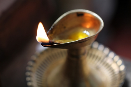 hinduismo: Sola llama ardiente en una lámpara de aceite de bronce sobre un fondo oscuro Foto de archivo