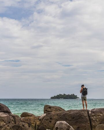 A backpacker is hiking along the coast, cloudy weather, ocean and rocks