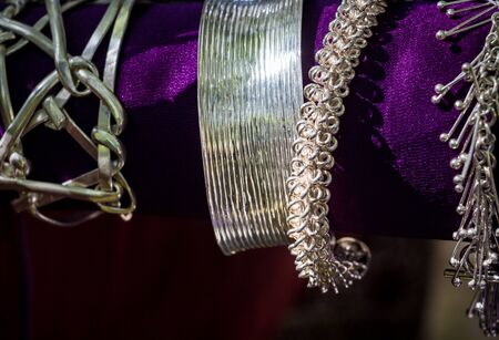 Silver jewelry is hanging on a purple background