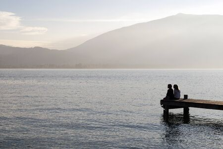 pontoon: People sat on a wooden pontoon looking at the horizon of a lake