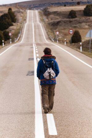 Woman walking alone on a long road.