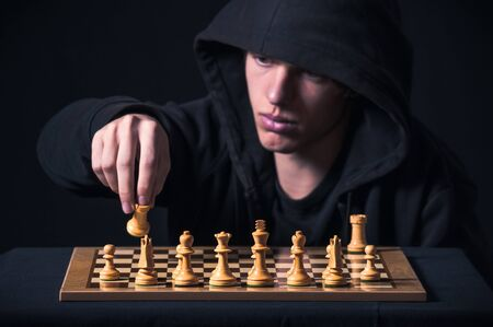 Blond boy with dark sweatshirt and hood photographed in studio, with black background, in front of a chess board Stok Fotoğraf