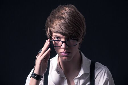 Blond boy with white shirt, suspenders and glasses photographed in studio with black background