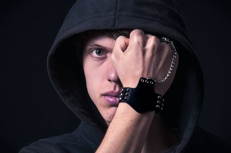 Blond boy with dark sweatshirt and hood photographed in studio with black background