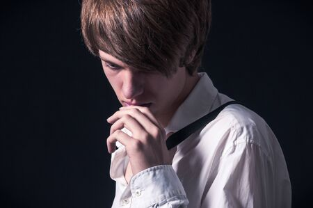Blond boy with white shirt and suspenders photographed in studio with black background