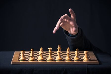 A hand emerges from the darkness to play a game of chess Banco de Imagens