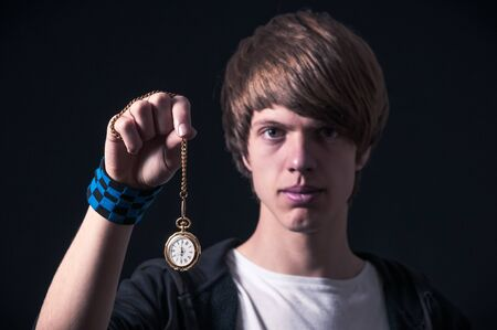 Blond boy with sweatshirt, showing a pocket watch with chain, photographed in studio with black background