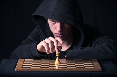 Blond boy with dark sweatshirt and hood photographed in studio, with black background, in front of a chess board Stock Photo