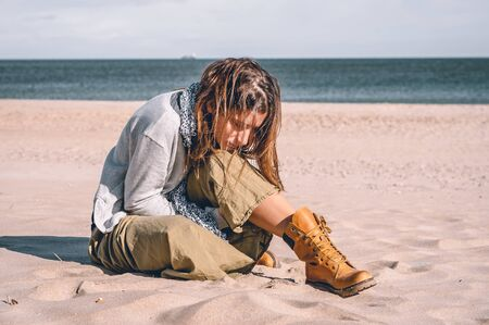 Young girl, wearing casual clothes, photographed on the beach in winter.
