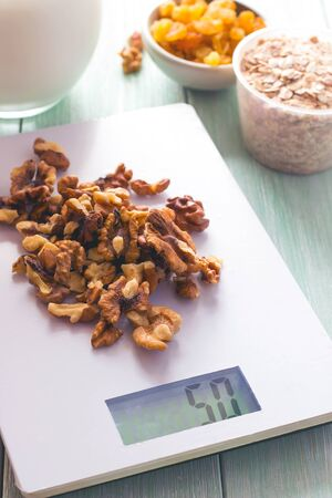 libra: oatmeal raisins walnut milk scale on a wooden table