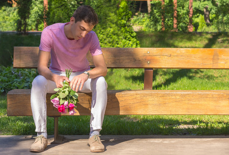 young men waiting date sitting on a bench with roses bouquet