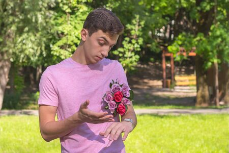 young men waiting date with roses watching time Stock Photo